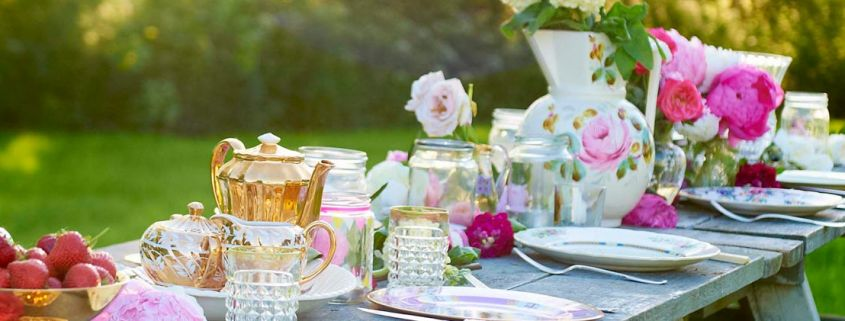 Close up of a luxury glamping picnic table laid with pretty pink floral crockery and flowers.