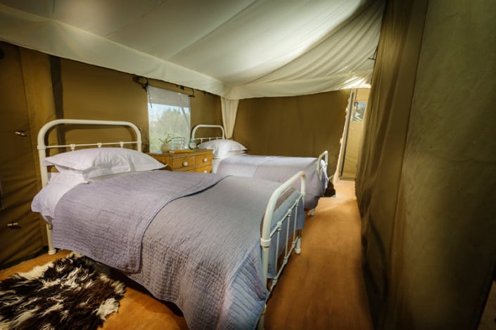 Luxurious twin wrought iron beds in the safari tents at Brownscombe Luxury Glamping in South Devon