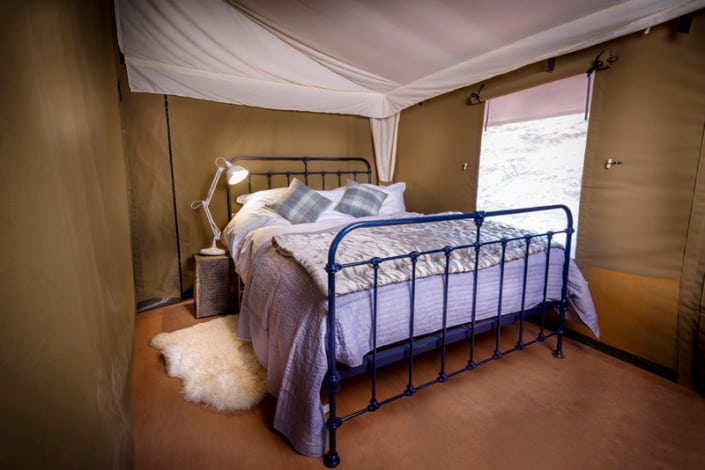 A beautiful wrought iron double bed with sumptuous bed linen at Brownscombe Luxury Glamping in the South Hams