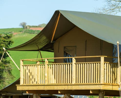 The front of one of the safari tents at Brownscombe Luxury Glamping with rolling green hills in the background