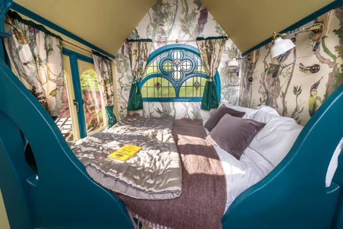 The beautiful stained glass window and luxurious double bed inside the Tabernacle at Brownscombe Luxury Glamping