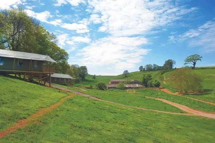 Two luxury glamping safari tents sitting in the lush green farm fields at Brownscombe in Devon